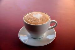 En cappuccinokopp på tabellen Royaltyfri Fotografi