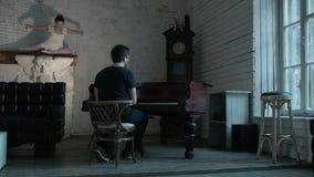 En castillo viejo el hombre juega el piano, y la bailarina misteriosa baila en la chimenea Un interior del vintage con almacen de video