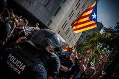 En catalan kravallpolis framme en pro-självständighetfolkmassa arkivbilder
