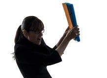 Affärskvinnan som skyddar bak mappar, sparar silhouetten Royaltyfri Foto