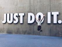 En Caucasian man som hoppar framme av precis, undertecknar det fotografering för bildbyråer