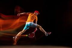 En caucasian man som spelar tennis på svart bakgrund royaltyfri fotografi
