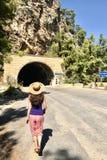 En caucasian ung brunettkvinna i en sugrörhatt går in mot en tunnel i bergen Bakre sikt, solig dag för sommar arkivbild