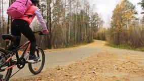 En caucasian väg för barnrittcykel i höst parkerar Går den svarta orange cirkuleringen för liten flickaridningen i skogunge att g arkivfilmer