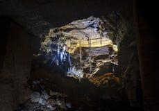 En caver undersöker en grotta med en lykta Odessa Catacombs Ukraina royaltyfri bild