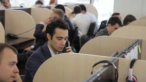 En centro de atención telefónica los consultores jovenes en trajes proporcionan ayuda económica almacen de video