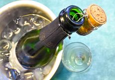 en champagneflaska i en kall hink med is och vatten, korkinnehavet från munnen som dekorerar platsen och en kopp med arkivbilder