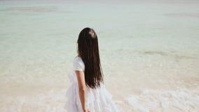 En charmig filippinsk skolflicka i en vit klänning promenerar en vit sandig strand Tycka om det tropiska landskapet lager videofilmer