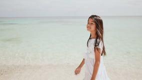 En charmig filippinsk skolflicka i en vit klänning promenerar en vit sandig strand Tycka om det tropiska landskapet arkivfilmer