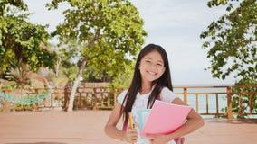 En charmig filippinsk skolflicka med en ryggsäck och böcker i en parkera av flickan för kust A poserar joyfully och att lyfta hen lager videofilmer