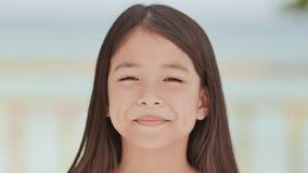 En charmig filippinsk skolflicka poserar positivt Vända mot närbilden på enblått bakgrund av en tropisk strand lager videofilmer
