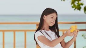 En charmig filippinsk skolflickaflicka i en vit klänning och ett långt hår poserar positivt med en mango i henne händer Baikal la arkivfilmer