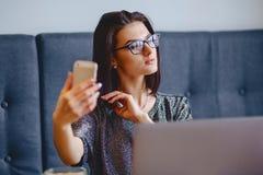 En charmig flicka i exponeringsglas för en bärbar dator som gör en selfie fotografering för bildbyråer