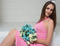 En charmig flicka med en vit- och blåttbukett av blommor på en vit marmortrappuppgång royaltyfria bilder