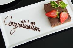 En chokladkaka med strawbery på en vit platta royaltyfri bild