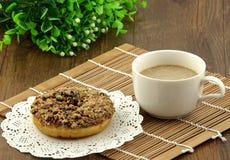 En chokladmunk och en kopp kaffe Arkivbilder