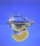 En citronskiva som plaskar in i vatten Royaltyfria Bilder