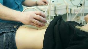 En clínica el doctor realiza a un blonde joven del ultrasonido abdominal almacen de metraje de vídeo