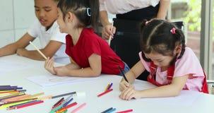 En clase de arte, los estudiantes asi?ticos dibujan consciente metrajes