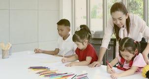 En clase de arte, los estudiantes asi?ticos dibujan consciente almacen de video
