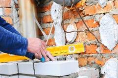 En closeup av en murarearbetare som installerar witekvarter och diktar tegelstenmurverket, fogar ihop den yttre väggen med mursle Royaltyfri Foto