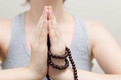 En closeup av en kvinna i yoga poserar och att rymma buddistiska pärlor i händer fotografering för bildbyråer
