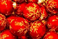 En closeup av röda julprydnader i en bunke royaltyfri foto