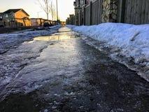 En closeupsikt av hal svart is som täcker en trottoar i ottan av en bostads- neighbourhood under vintern arkivfoton