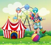 En clown som balanserar ovanför en uppblåsbar boll på karnevalet Royaltyfri Bild