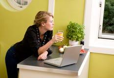 En cocina con la computadora portátil Foto de archivo libre de regalías