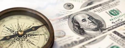 En collage med kompasset och US dollarräkningar Arkivbild