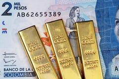 En colombiansk tvåtusen peso sedel med tre guld- stänger arkivbilder