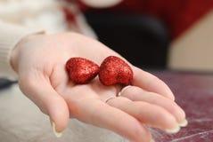 En corazones decorativos de las manos femeninas delicadas Imagen de archivo