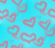 En corazones rosados y rojos de un fondo azul Imagen de archivo libre de regalías