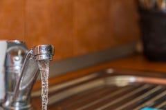 En coulant, nettoyez, eau du robinet fraîche à l'évier de cuisine photos stock