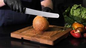 En coupant les petits pains avec les graines de sésame avec un couteau de cuisine sur le conseil en bois, noircissez le fond banque de vidéos