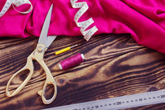 En cousant des outils, dentelez le tissu et filetez sur un fond en bois Image stock