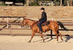 En cowboy som rider hans häst i en arena Arkivbild