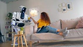 En cyborg kommer med ett flickaexponeringsglas av fruktsaft lager videofilmer