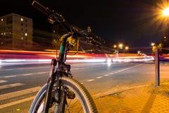 En cykel på gatan i en natt mot en bakgrund av oskarpa ljus från bilar, ljuset skuggar på gatan fotografering för bildbyråer