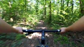 En cykla flicka rider en cykel i en skog på en grusväg arkivfilmer