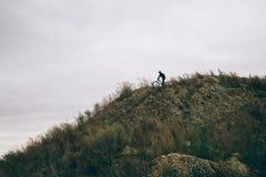 En cyklist överst av kullen Arkivbilder