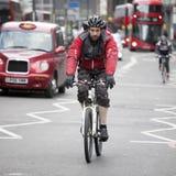 En cyklist i ett rött omslag rusar bland bilarna på vägen Royaltyfri Foto