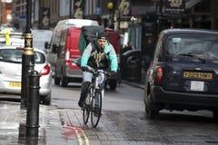 En cyklist i ettgräsplan omslag och med en påse Fotografering för Bildbyråer