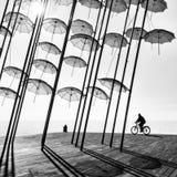 En cyklist och en flicka under paraplyerna royaltyfri fotografi