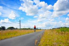 En cyklist på en tom lantlig väg Royaltyfri Bild