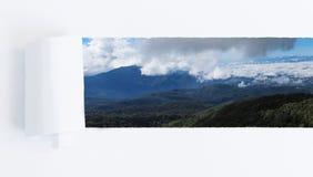 En déchirant un trou de papier de cadre pour indiquer la montagne et le ciel aménagez en parc Photo stock