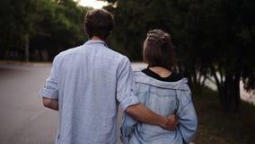 En dépistant la longueur d'un jeune couple chacun des deux dans des chemises semblables bleues soyez liaison de marche par le par banque de vidéos