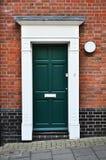 En dörr i en tegelstenvägg Arkivbild