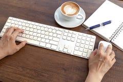 En dactylographiant et ayez une tasse de café de forme de coeur d'art de latte sur en bois Photographie stock